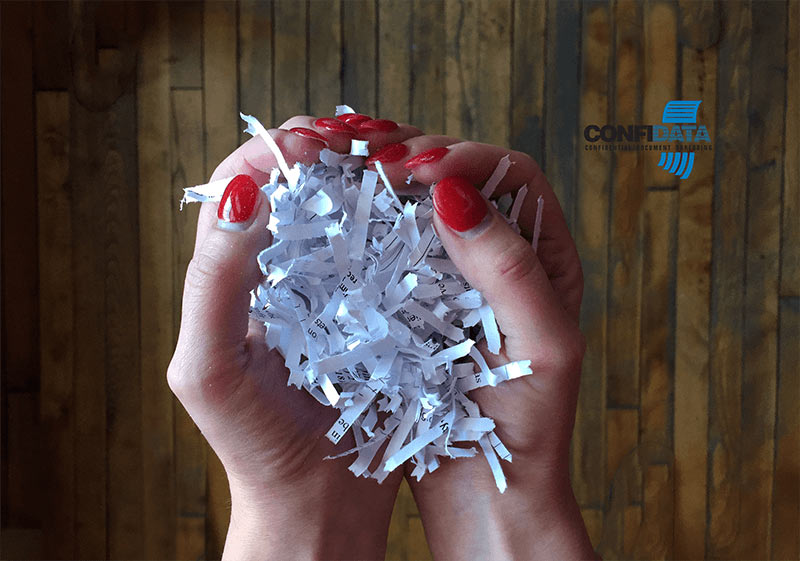shredded paper in a person's hand making the shape of a heart