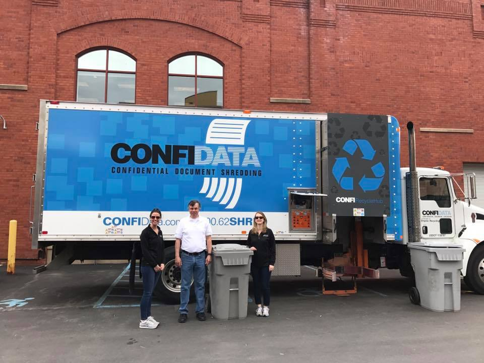 Confidata team posing by their mobile shredding truck at a Saratoga shred event