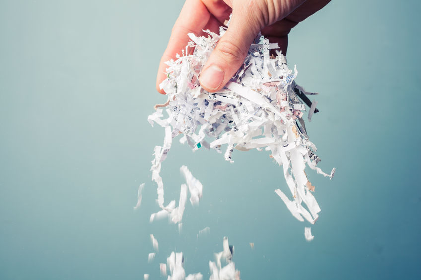 hand holding a bunch of shredded paper
